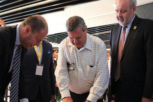 Vision Australia CEO Ron Hooton, with Bill Jolley and Josh Frydenberg inspecting a $50 note