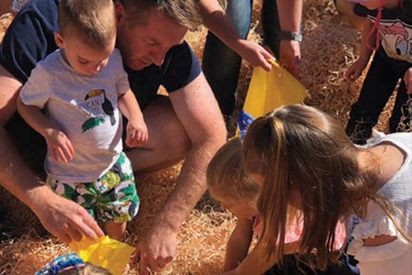 Parents helping children hunt for easter eggs in hay